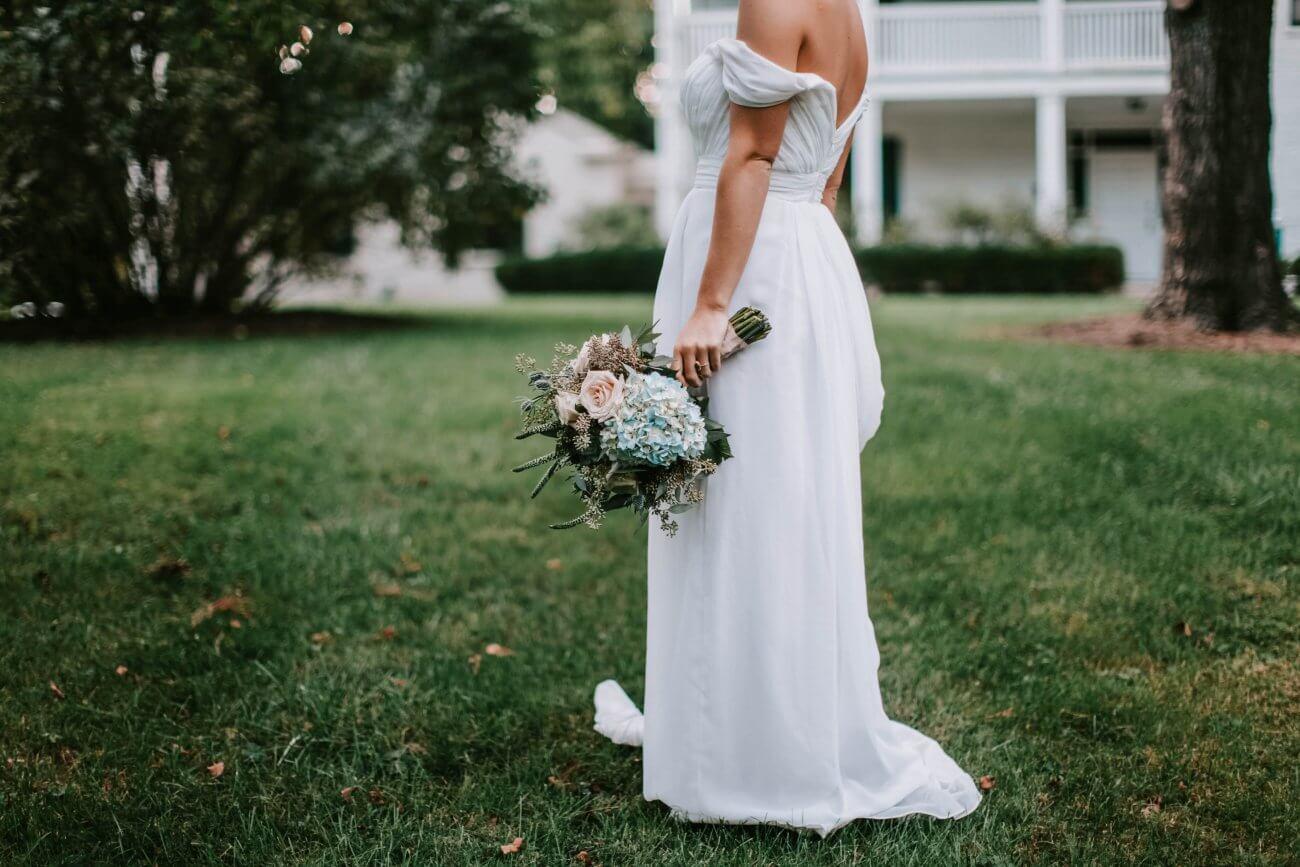 en brud i hvid brudekjole står med sin brudebuket i en alternativ brudekjole